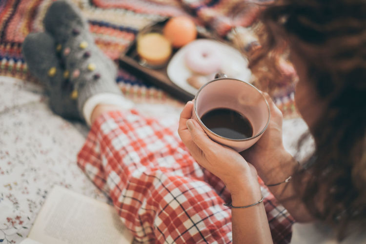 High angle view of woman holding coffee cup on bed
