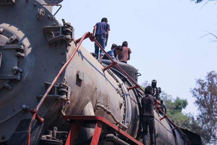 Low angle view of boys climbing freight train against clear sky