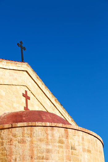 Low angle view of cross on building against clear blue sky