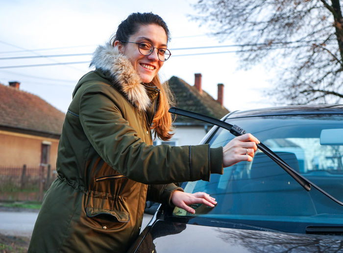 Portrait Of Smiling Young Woman Holding Windshield Wiper In Town