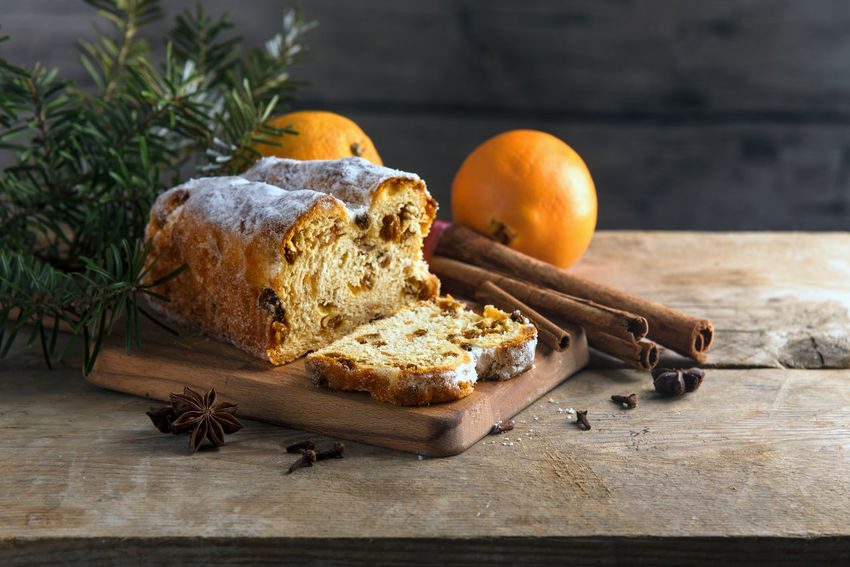 Christmas cake, in germany christstollen with fir branches, oranges, cinnamon and anise stars on a rustic table, wooden vintage background with copy space Christmas Rustic Christstollen Cinnamon Cutting Board Day Fir Branches Food Food And Drink Freshness Indoors  No People Oranges SLICE Wooden