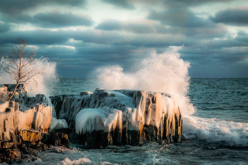Waves Breaking On Rocks At Coast