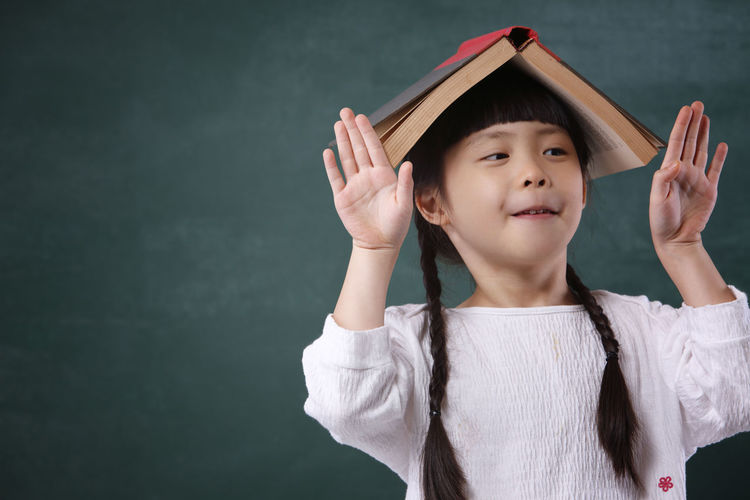 Girl With Book On Head Standing By Blackboard