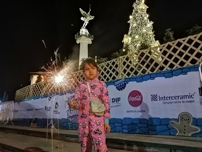 Full length of boy standing by illuminated christmas lights at night