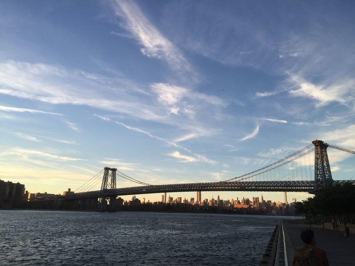 Williamsburg bridge over east river against sky during sunset
