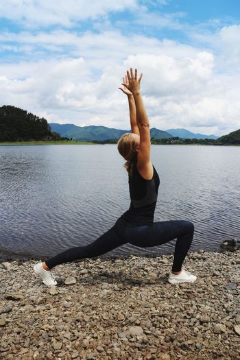Woman with arms raised exercising by lake