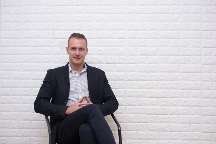 Portrait of businessman sitting on chair against white brick wall