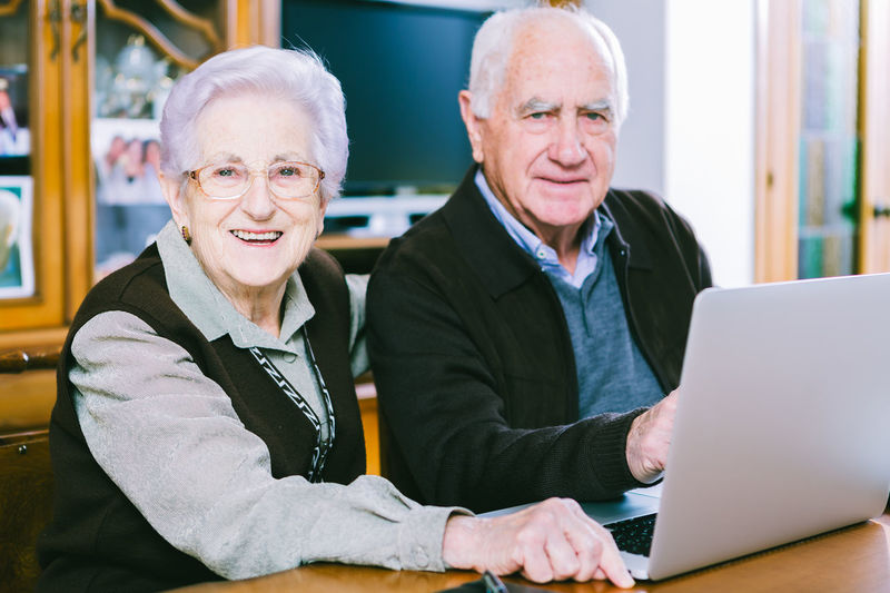 Couple of seniors surfing the net with a laptop at home. Cheerful Communication Eyeglasses  Happiness Indoors  Laptop Lifestyles Looking At Camera Mature Men Men Occupation Portrait Real People Senior Adult Senior Men Senior Women Sitting Smiling Table Technology Togetherness Two People Using Laptop Wireless Technology Working