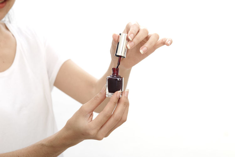 Midsection of woman holding nail polish bottle against white background