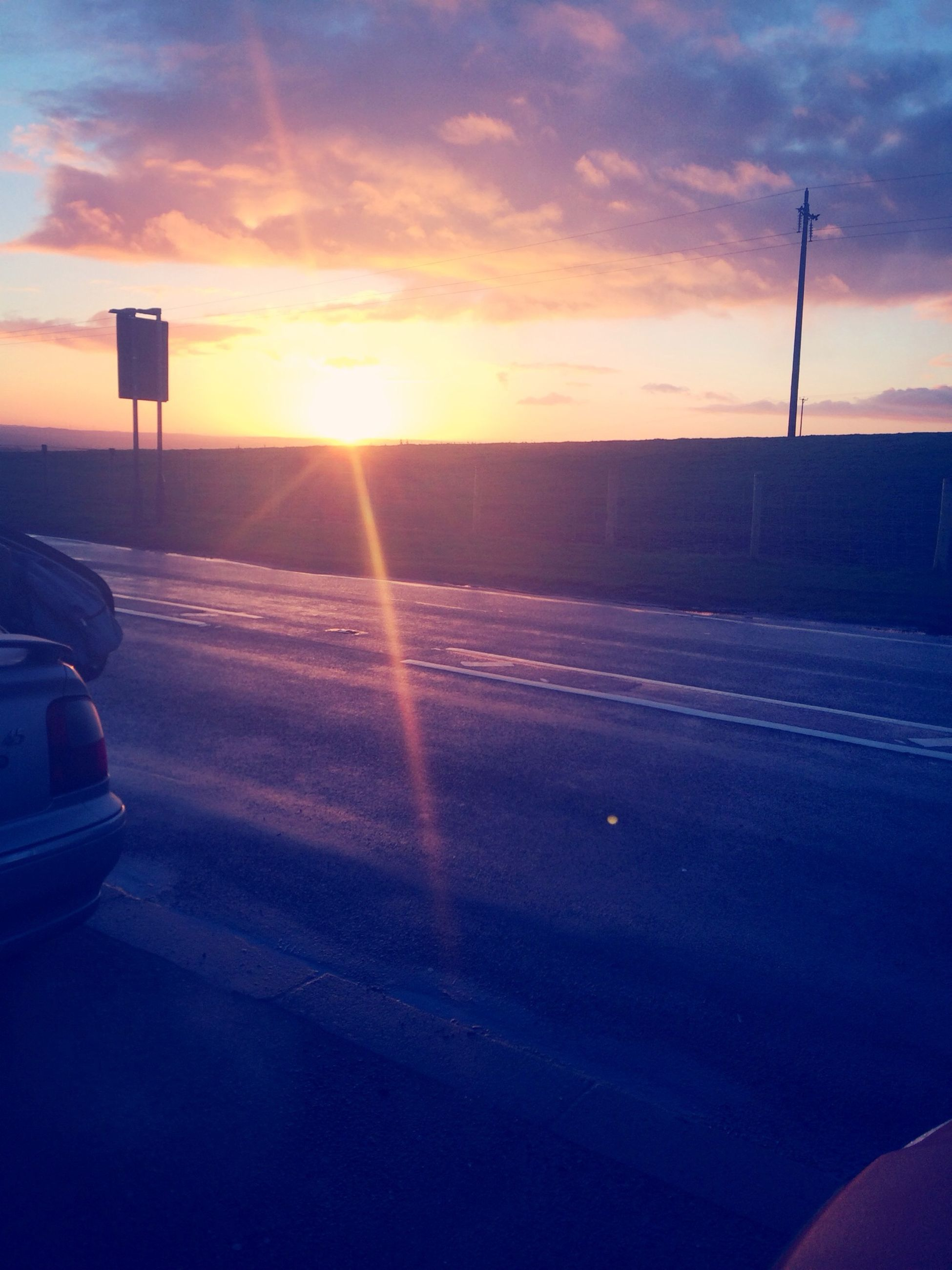 sunset, transportation, sky, sun, car, land vehicle, mode of transport, road, cloud - sky, orange color, scenics, sunlight, beauty in nature, street, nature, cloud, lens flare, tranquility, sunbeam, tranquil scene