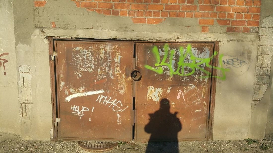 Self Portrait against a Rusted Metal  Door with Grafitti in Radom Poland . City Life Drain Cover Shadows And Light