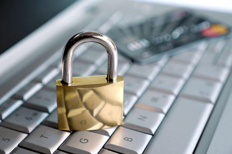 High angle view of padlock and credit card on keyboard