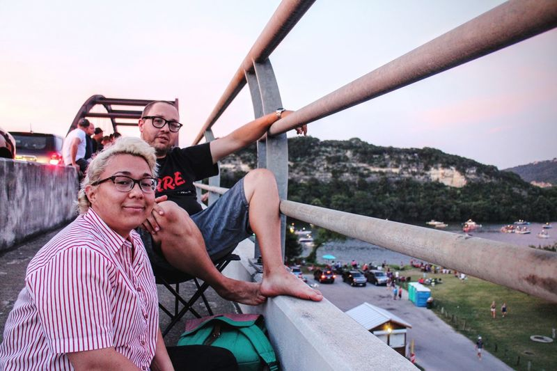 Portrait Of Friends Relaxing By Railing