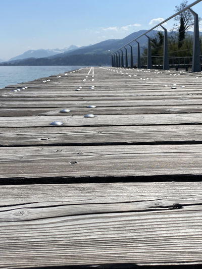 Surface level of wooden pier on sea against sky