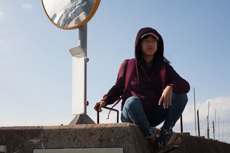 Low angle view of young woman sitting against clear sky