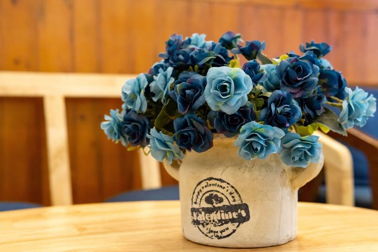 Beautiful plastic flower in cafe. Coffee Shop Blue Flowers Bouquet Bunch Of Flowers Cafe Close-up Day Decoration Flower Flower Arrangement Flower Head Flower Pot Flowering Plant Focus On Foreground Freshness Indoors  No People Plant Plastic Flower Rosé Table Text Vase Wood - Material