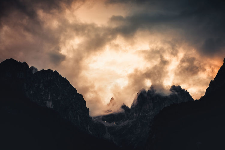 Low angle view of silhouette mountains against dramatic sky
