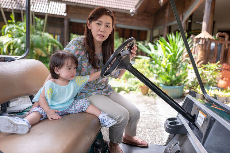 Portrait Of Woman Sitting With Daughter On Golf Cart
