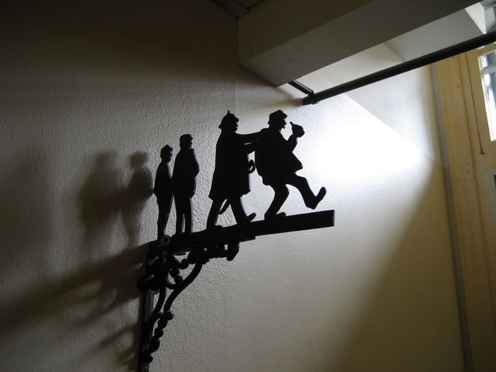 Decoration depicting a police officer apprehending a drunkard casting a shadow on the wall near the entrance to Falu fängelse vandrarhem (Falu prison youth hostel). The youth hostel was previously a prison also known as Länscellfängelset i Falun and Straffängelset i Falun. In Falun, Sweden Drunk Drunkard Falun Police Officer Sweden Law Law Enforcement Men Prison Shadow Silhouette Youth Hostel