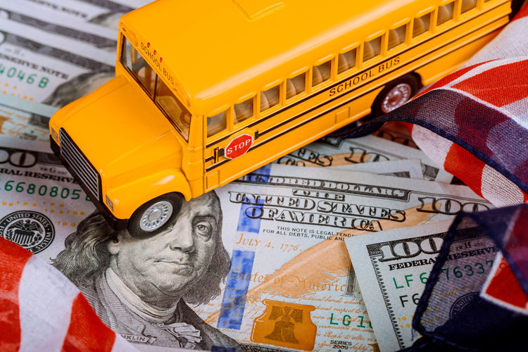 toy yellow school bus , US flag and dollar cash money American Flag Business Dollar Sign HUNDRED School Bus Stop School Buses America American Culture Car Cash Close-up Dollar Finance Finance And Economy Focus On Foreground Indoors  Mode Of Transportation Money No People School School Bus Transportation Wealth Yellow