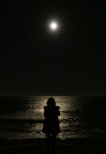 Silhouette of woman looking at sea against sky