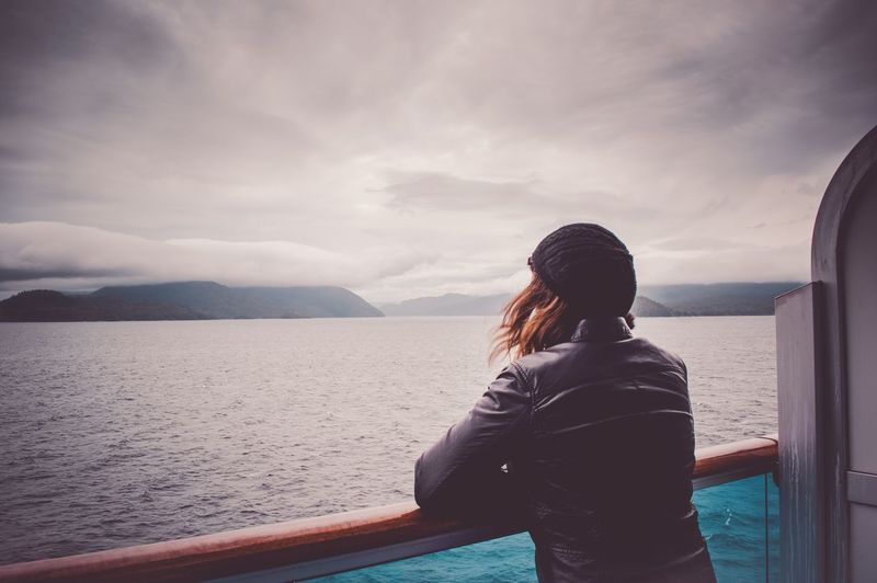 Woman looking at sea while leaning on railing in boat