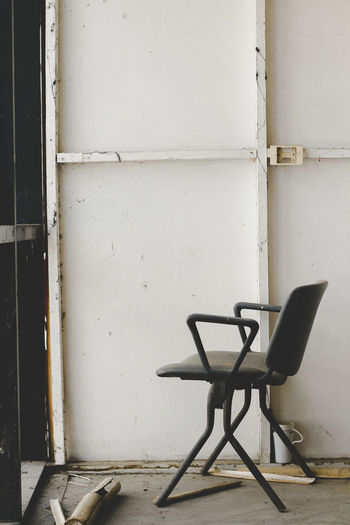 Empty chair on table against wall in old building
