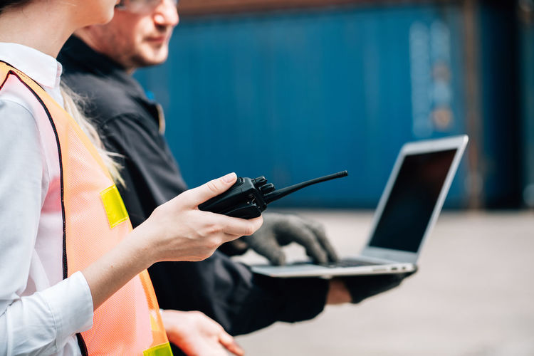 Midsection of woman holding walkie-talkie by man using laptop