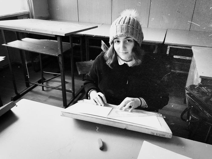 Portrait of young woman wearing knit hat studying at home