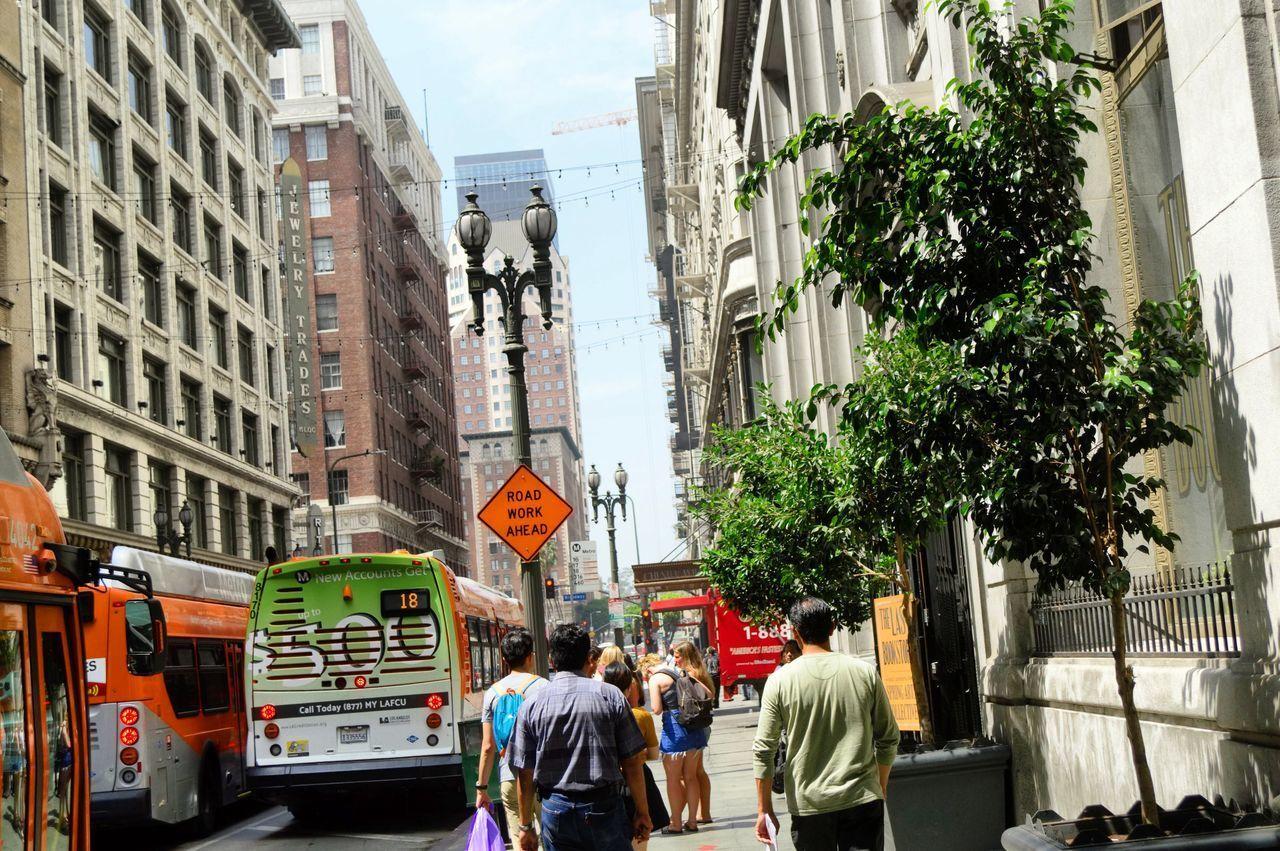 PEOPLE ON STREET IN CITY AGAINST BUILDINGS