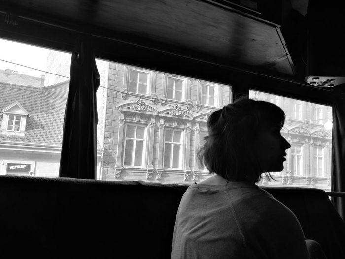 Rear view of woman looking away while sitting in van