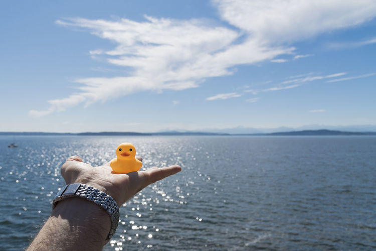 Cropped image of hand holding rubber duck against sea at beach