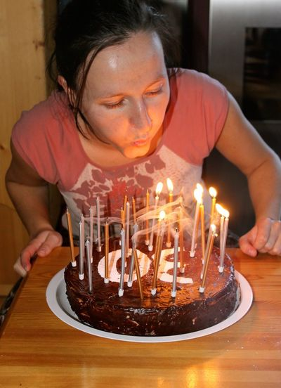 Woman blowing lit candles on birthday cake at table