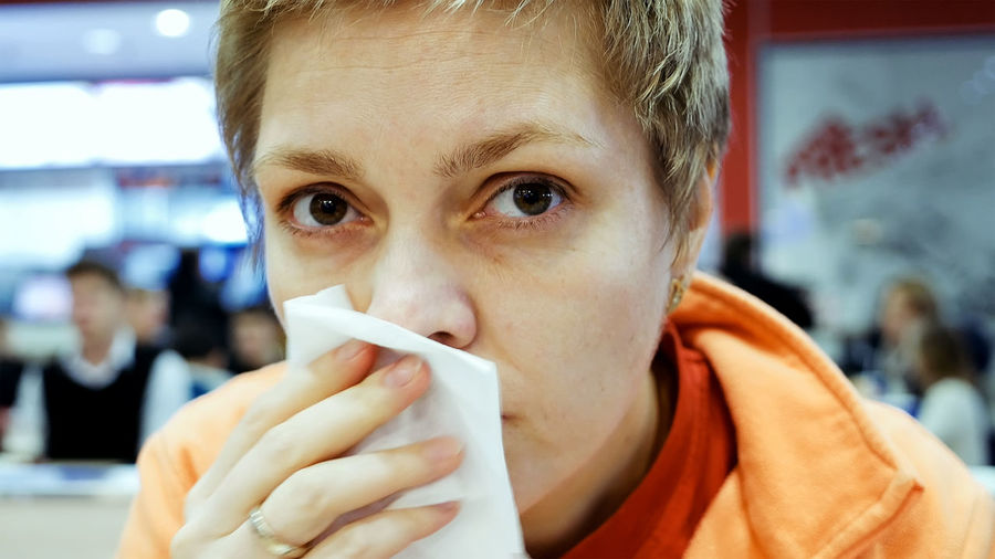 Close-up portrait of woman sneezing at restaurant