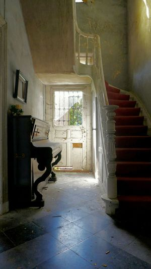 Grand piano by staircase at abandoned home