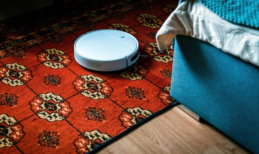 Robot vacuum cleaner and mop cleaning carpet in bed room floor. modern smart device housekeeping.