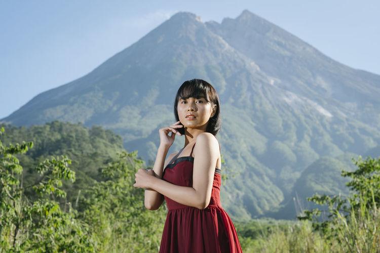 Full length of woman standing on rocks against mountain