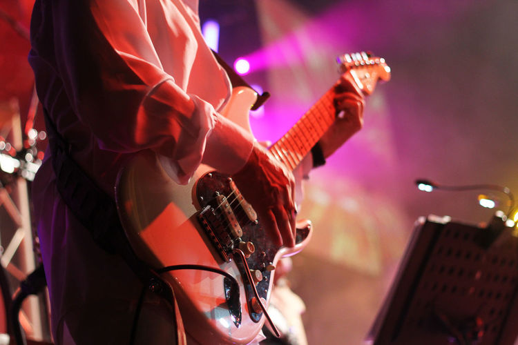 Midsection Of Man Playing Guitar In Music Concert