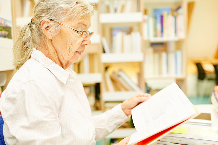 Side view of woman with book on table