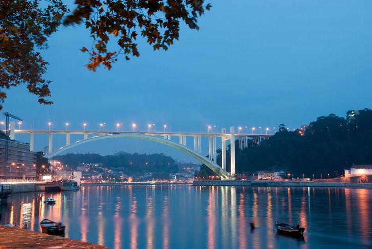 Illuminated bridge over calm river against clear blue sky