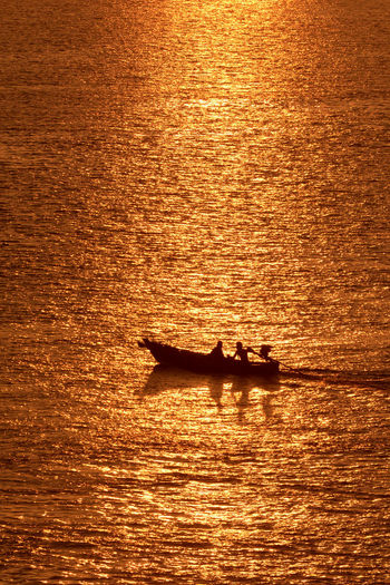 SILHOUETTE OF TWO PEOPLE IN A BOAT AT SUNSET