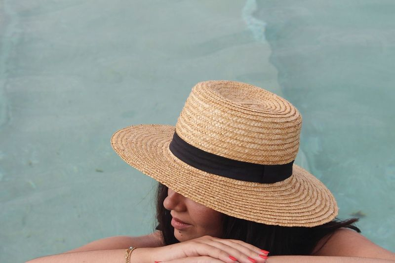 Midsection of woman relaxing in swimming pool against sea