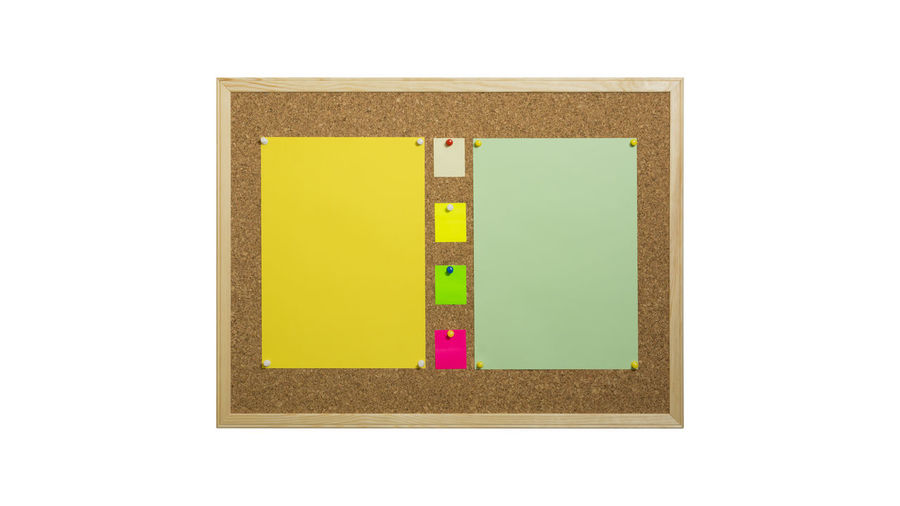 Close-up of blank papers on bulletin board against white background