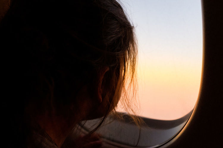 Close-up portrait of woman against sky during sunset