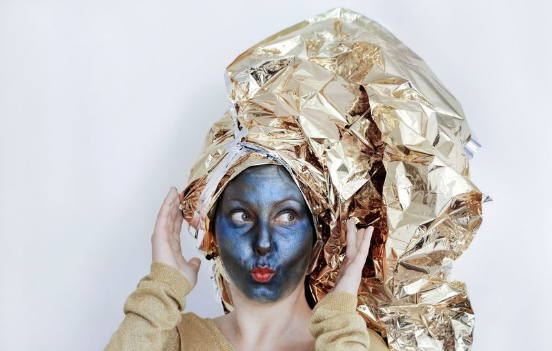 Close-Up Of Young Woman With Face Paint Covering Hair In Crumpled Golden Foil Against White Background