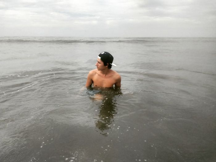 Shirtless young man in sea against sky