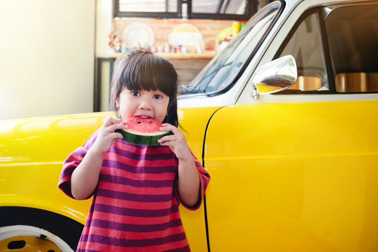 Kids Eating Watermelon in Summer. Girl enjoying her Sweet Fruit. Retro Car and Garage Decor as background One Person Real People Childhood Casual Clothing Front View Food And Drink Child Portrait Lifestyles Holding Looking At Camera Yellow Car Mode Of Transportation Innocence Transportation Day Land Vehicle Bangs Drinking Hairstyle Girl Watermelon Summer Time  Retro Garage