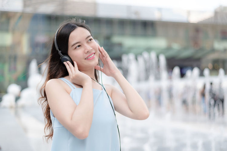 Beautiful young woman using phone while standing outdoors