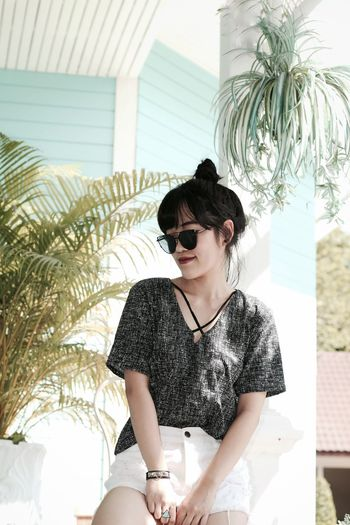 Young woman sitting on sunglasses