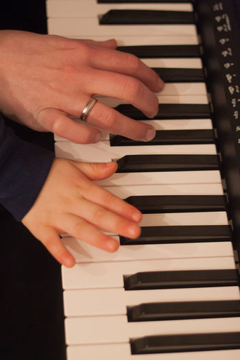 Cropped Image Of Mother And Child Playing Piano
